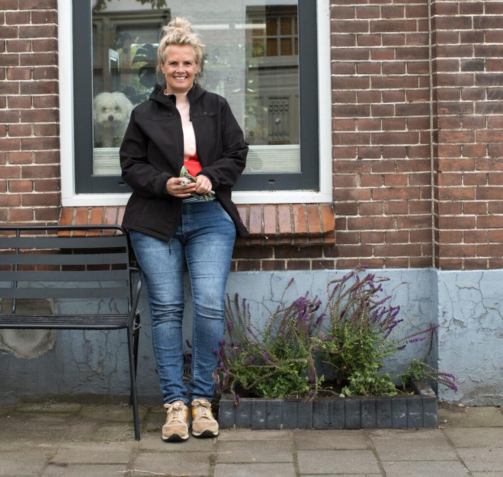 vrouw leunt tegen haar woning waar een geveltuintje is aangelegd